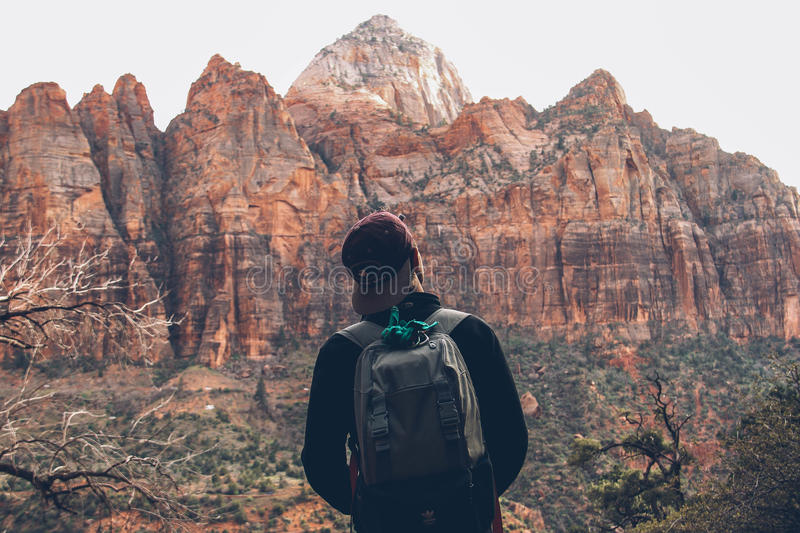 Man Wearing Gray Backpack Standing In Front Of Rocky Mountain During Daytime Free Public Domain Cc0 Image