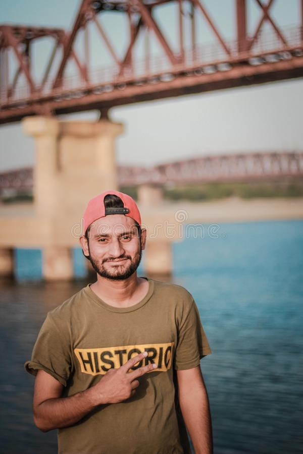 Man Wearing Gray Historic-printed T-shirt and Red Snapback Cap Taking Photo Beside Body of Water stock image