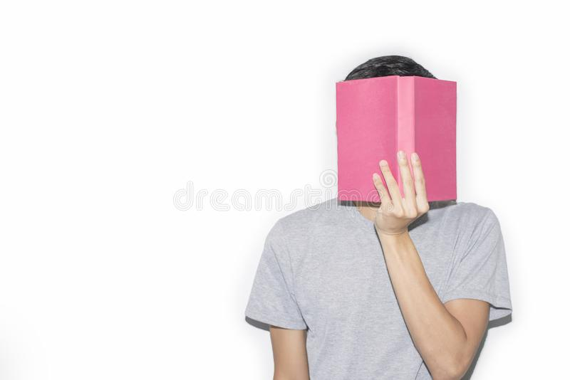 Man wearing a gray T-shirt holds his book off his face. On a white background, Copy-space royalty free stock images