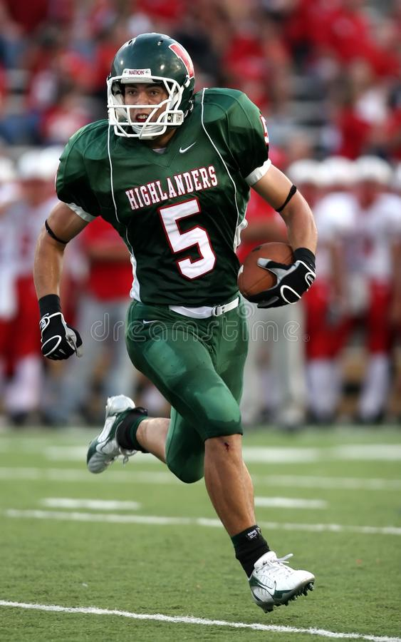 Man Wearing Green American Football Jersey Holding the Ball While Running on the Field stock photo