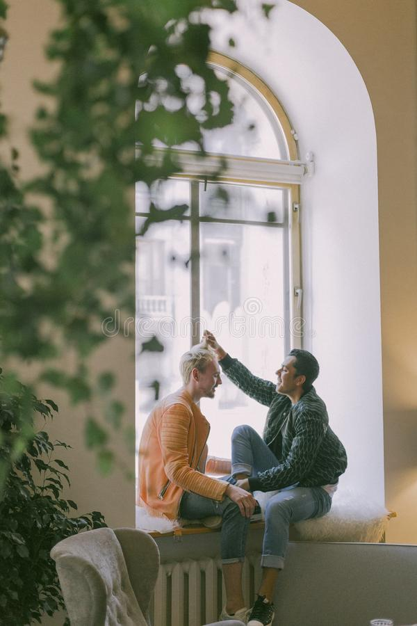 Man Wearing Green Jacket in Front of Man Wearing Orange Zip-up Jacket Sitting on Near the Window Photo stock photo