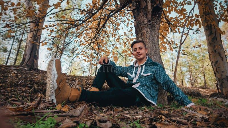 Man Wearing Green Jacket Sitting on Ground Near Tree royalty free stock photos