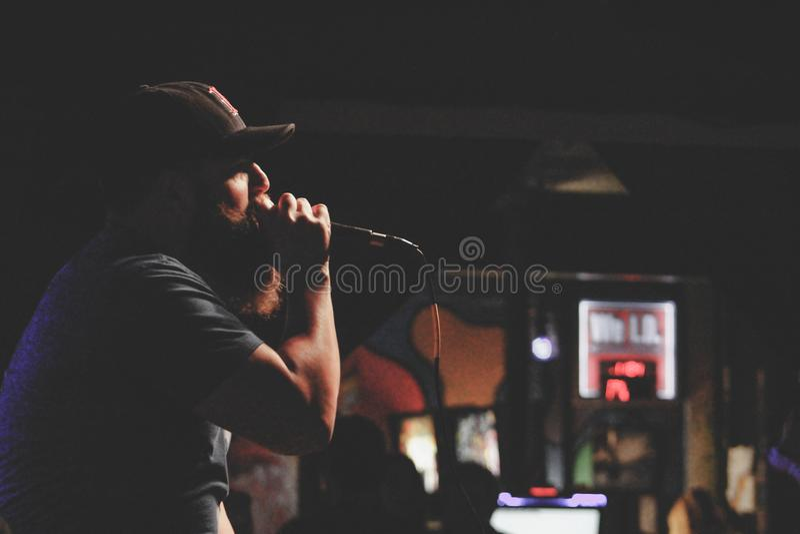 Man Wearing Grey Shirt and Black Cap Singing Using Corded Microphone royalty free stock image