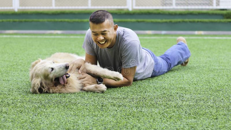 Asian man lay down on the green grass playing with his dog stock image