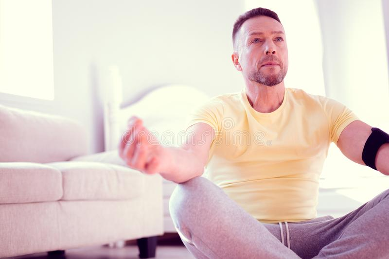 Man wearing grey trousers and yellow shirt sitting in lotus position meditating. Lotus position. Bearded mature man wearing grey trousers and yellow shirt royalty free stock photo