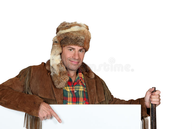 Man wearing a hat pointing to a blank poster. Man wearing a fur hat pointing to a blank poster royalty free stock image