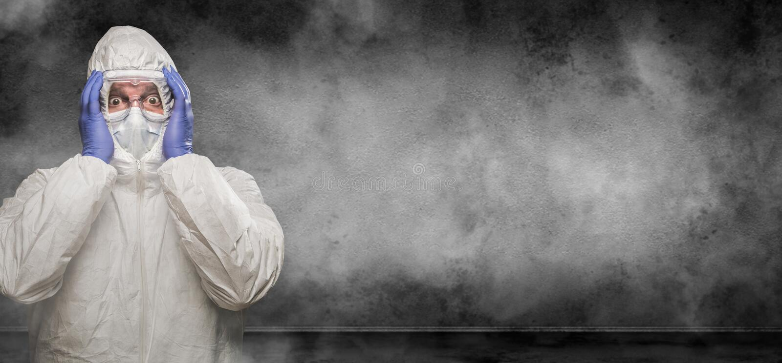 Man Wearing Hazmat Suit and Goggles In Smokey Room Banner with Copy Space royalty free stock photo