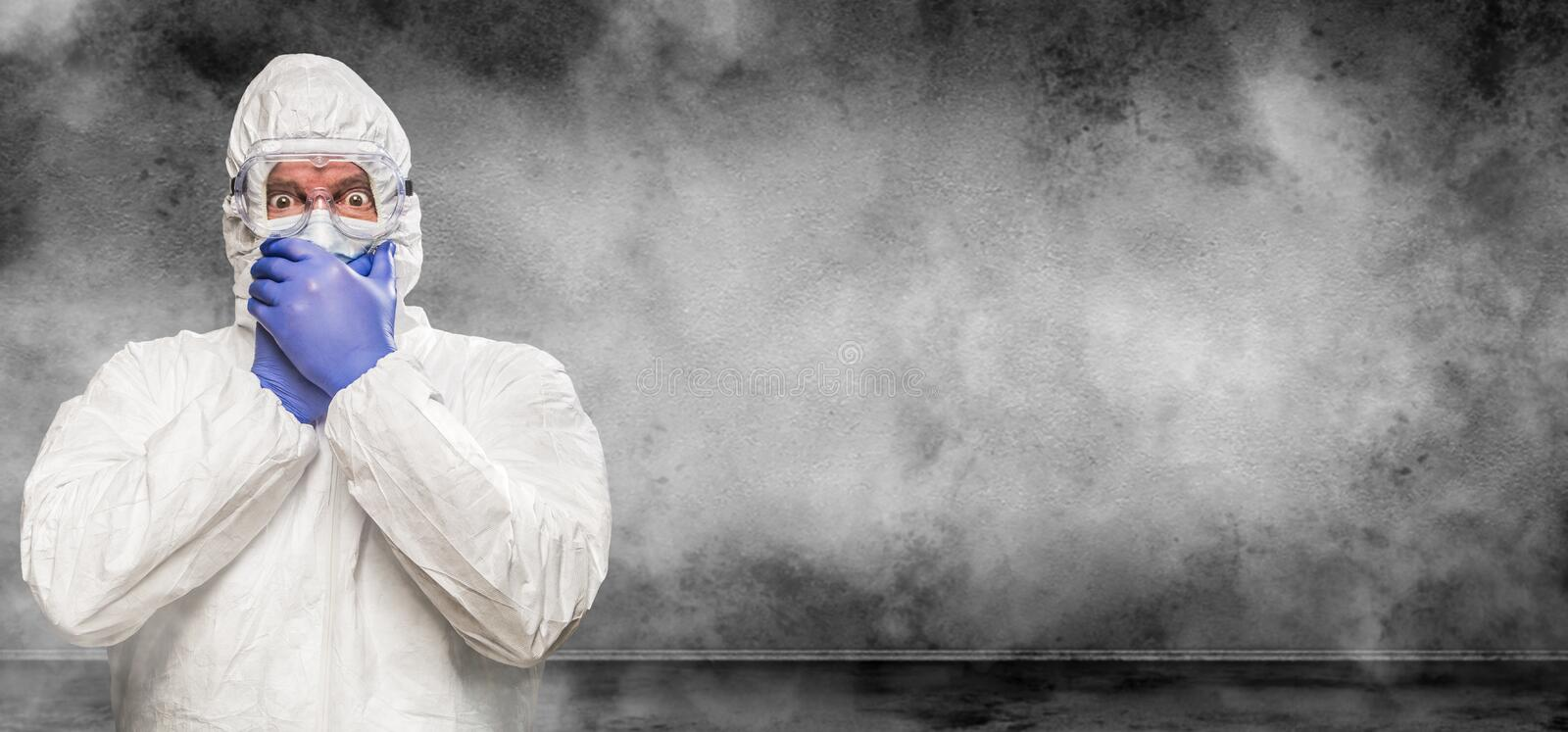 Shocked Man Wearing Hazmat Suit and Goggles In Smokey Room Banner with Copy Space royalty free stock photos