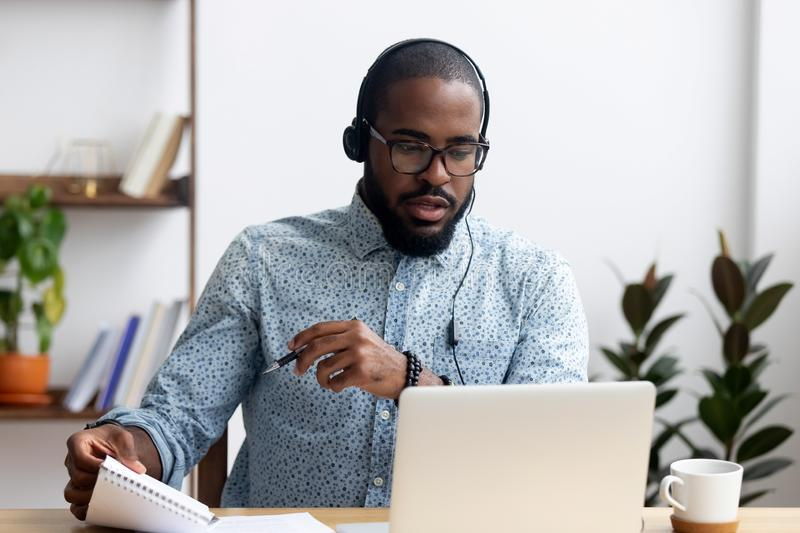 Man wearing headphones learn foreign language indoors. Black young man sitting at table wearing headphones learn foreign language improves knowledge looking at royalty free stock images