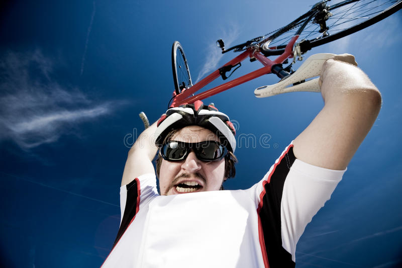 Man Wearing Helmet And Lifting Bicycle Into Air royalty free stock photography