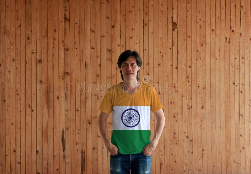 Man wearing India  flag color shirt and standing with two hands in pant pockets on the wooden wall background. Tricolor of India saffron orange white and green stock photography