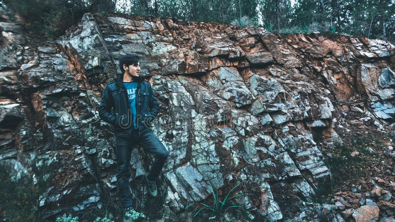 Man Wearing Jacket Standing in Stone Ledge stock images