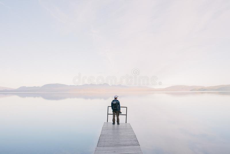 Man Wearing Jacket Standing on Wooden Docks Leading to Body of Water stock photography
