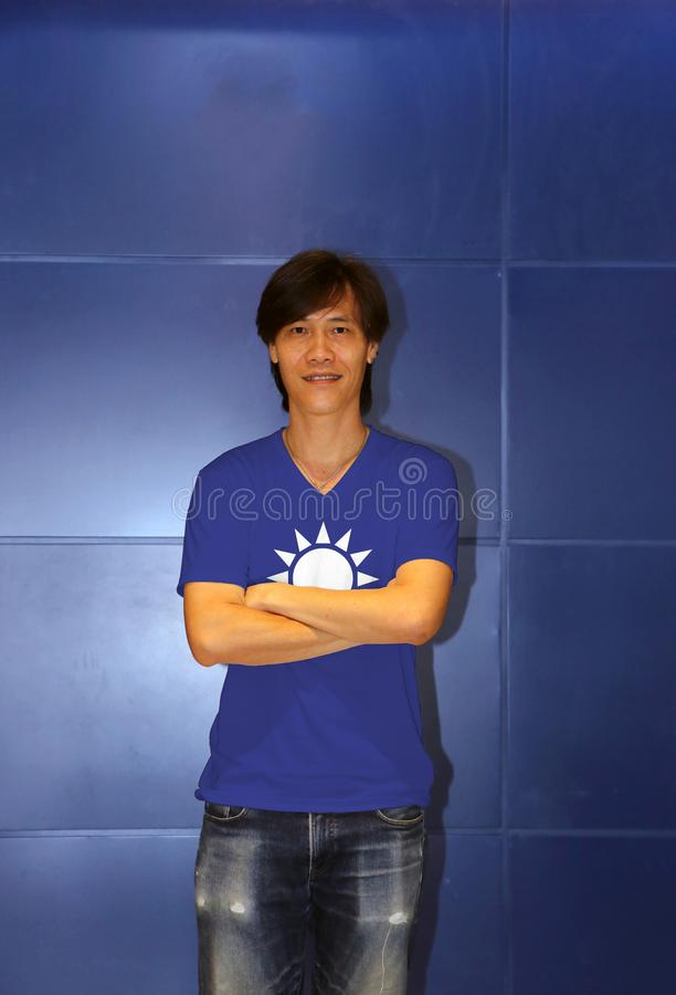 Man wearing Kuomintang flag on shirt and standing on the blue wall background. A white Sun with twelve rays on blue background royalty free stock photo