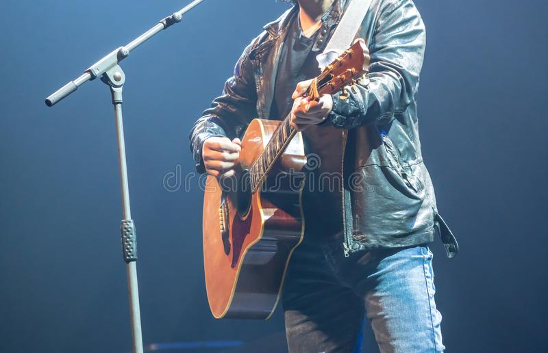 Man wearing leather jacket playing acoustic guitar on stage stock images