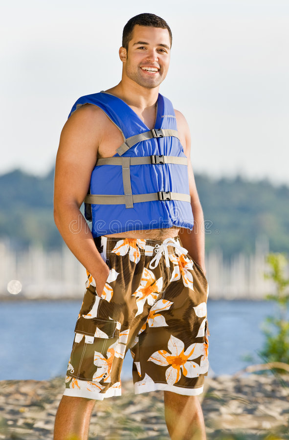 Man wearing life jacket at beach stock photos