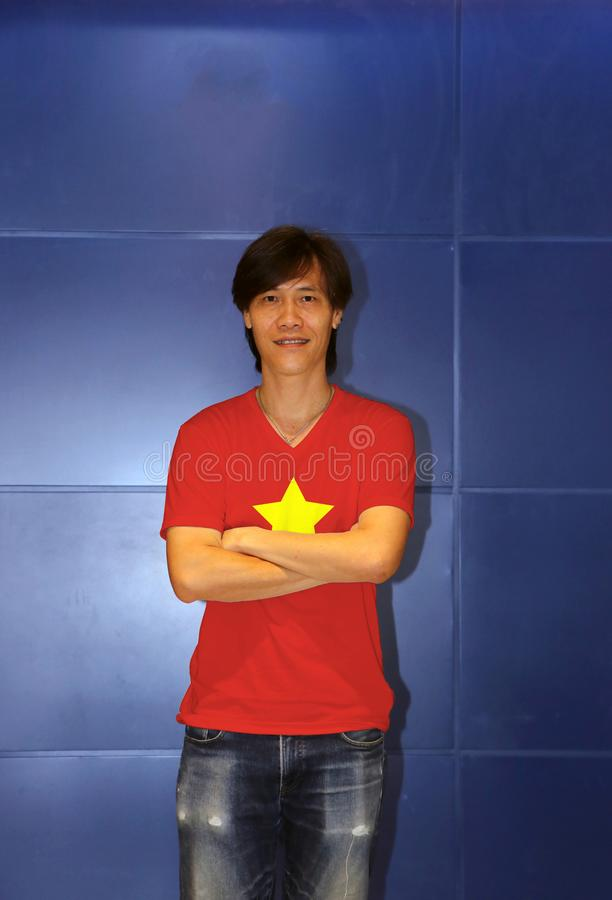 Man wearing North Vietnam 1945 to1955 flag on shirt and cross one`s arm on the blue wall background. Flag of Democratic Republic of Vietnam yellow star on red stock image
