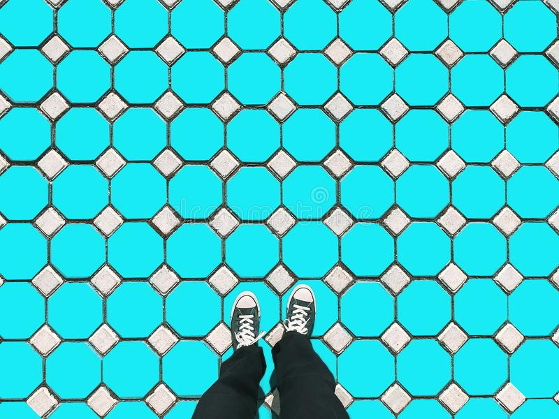 Man wearing old blue sneakers in blue trousers standing on hexagon floor fashion design concept, modern. pattern background stock image