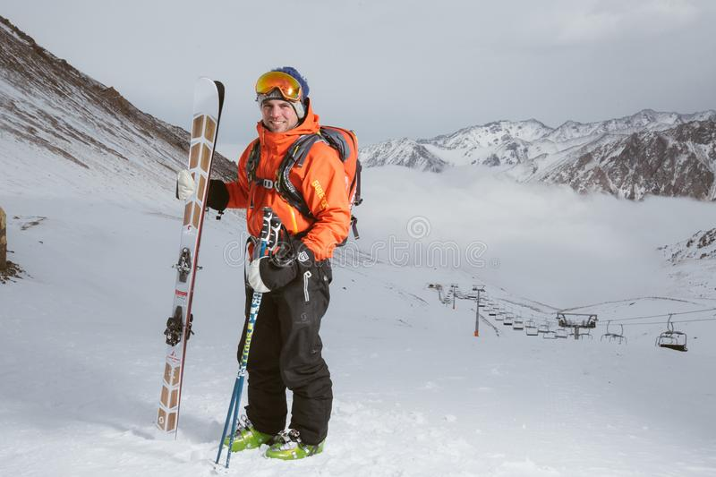 Man Wearing Orange and Black Snowsuit With Ski Set on Snow Near Cable Cars stock photography