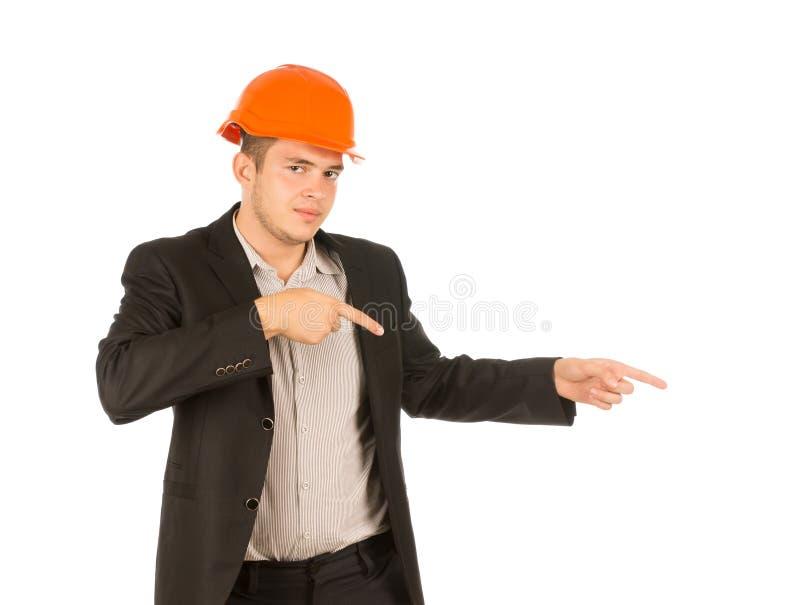 Man Wearing Orange Hard Hat Pointing to the Side. Man Wearing Orange Hard Hat and Suit Jacket Pointing to the Side and Looking at the Camera royalty free stock images