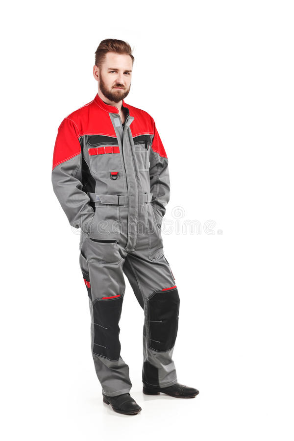 Man wearing overalls with red helmet stock image