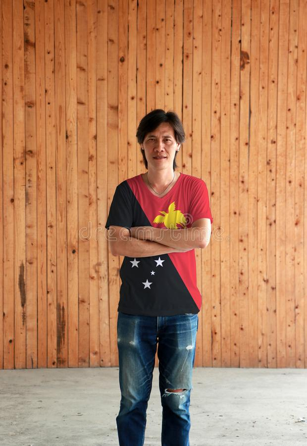 Man wearing Papua New Guinea flag color shirt and cross one`s arm on wooden wall background stock photos