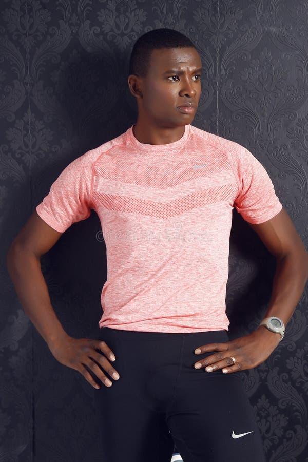 Man Wearing Pink Crewneck Shirt and Black Nike Shorts Standing royalty free stock photography