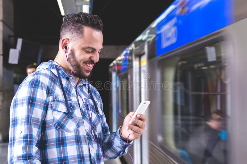 Man wearing plaid shirt reading articles and posts on his social. Young bearded man wearing plaid shirt reading articles and posts on his social media page in stock images