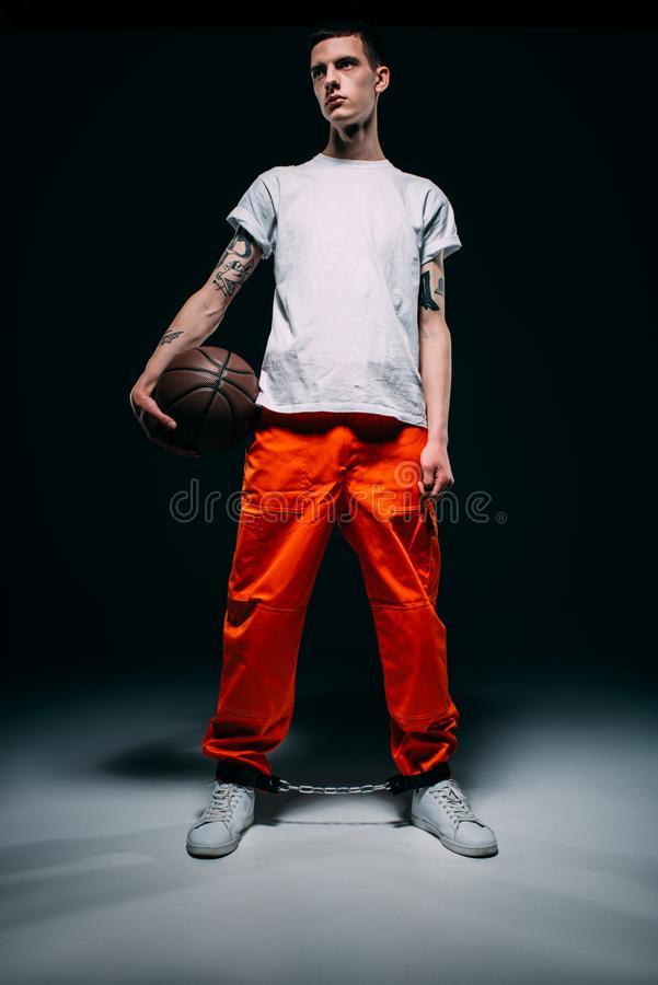 Man wearing prison uniform and cuffs holding basketball ball. On dark background royalty free stock photography