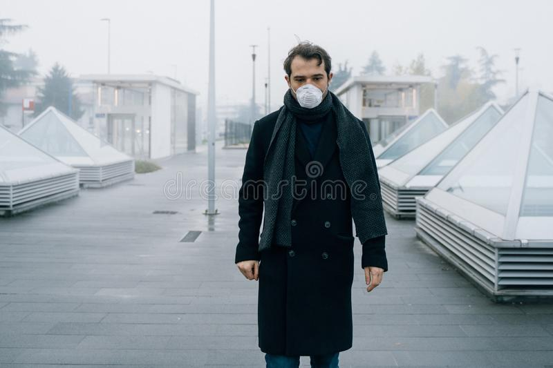 Man walking in city wearing mask against smog air pollution royalty free stock image