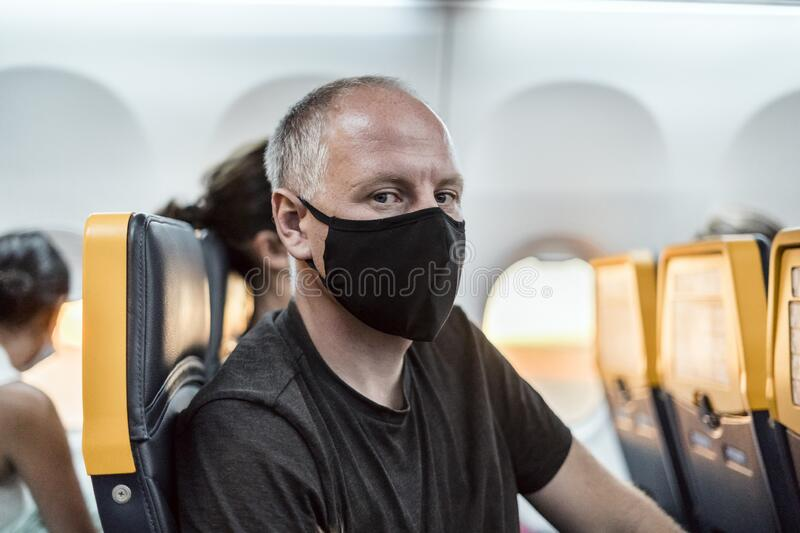 Man wearing face mask sitting in the airplane stock photo