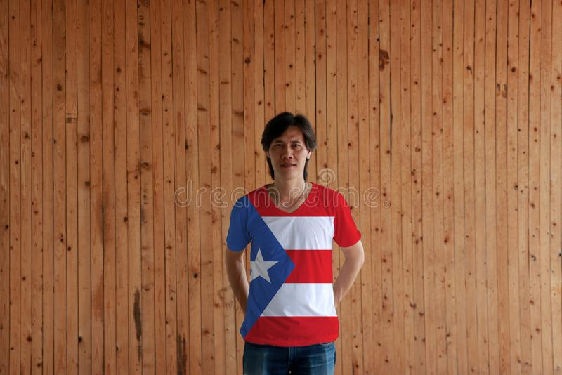 Man wearing Puerto Rico flag color of shirt and standing with crossed behind the back hands on the wooden wall background. Horizontal white and red bands with royalty free stock photography