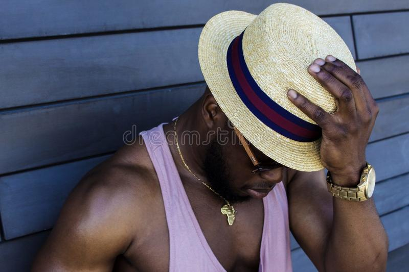 Man Wearing Purple Tank Top, Gold-colored Necklace, Gold-colored Watch, Sunglasses, and Beige Fedora Hat Outfit stock photo