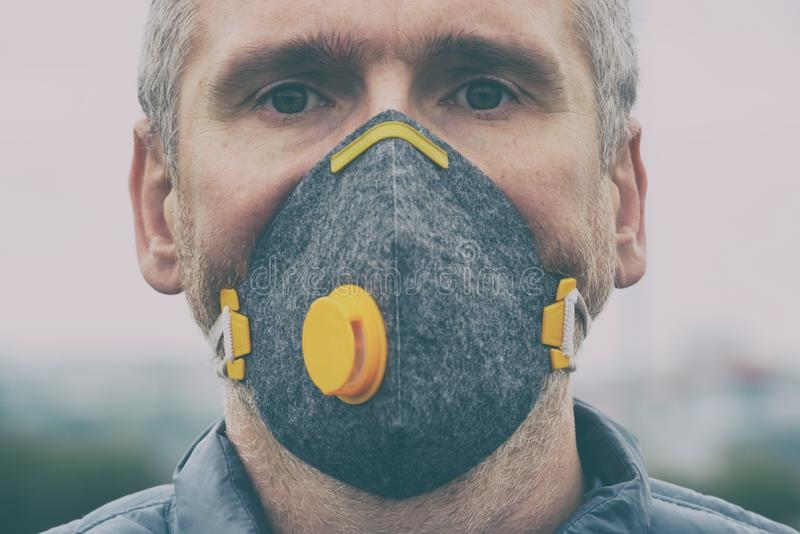 Man wearing a real anti-pollution, anti-smog and viruses face mask stock photos