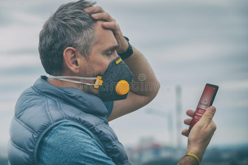 Man wearing a real anti-smog face mask and checking current air pollution with smart phone app stock photography
