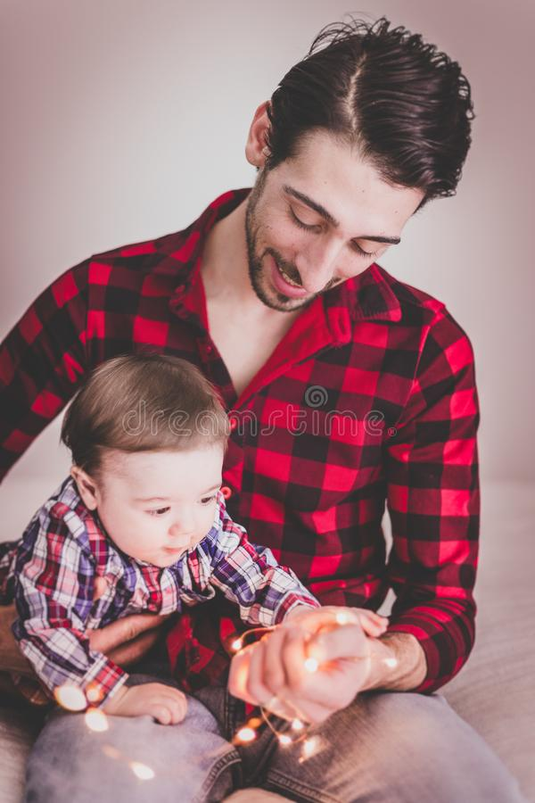 Man Wearing Red and Black Gingham Sports Shirt With Baby Beside Him stock images