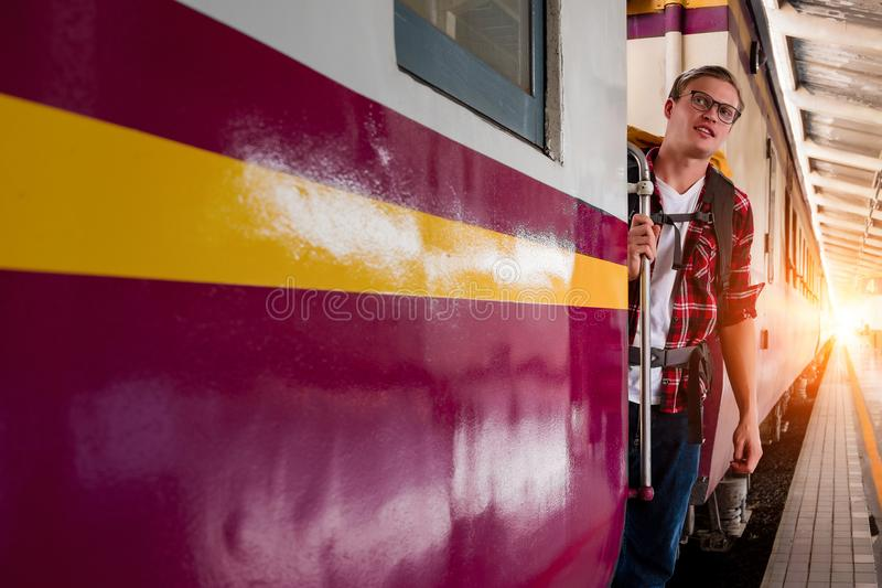 Man Wearing Red Button-up Shirt and Blue Jeans Holding Silver Train Side Rail stock images
