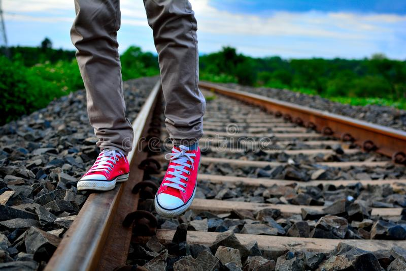 Man wearing red converse shoes and standing on the railway track. This picture consists of a Man wearing red converse shoes and walking on the railway track stock images