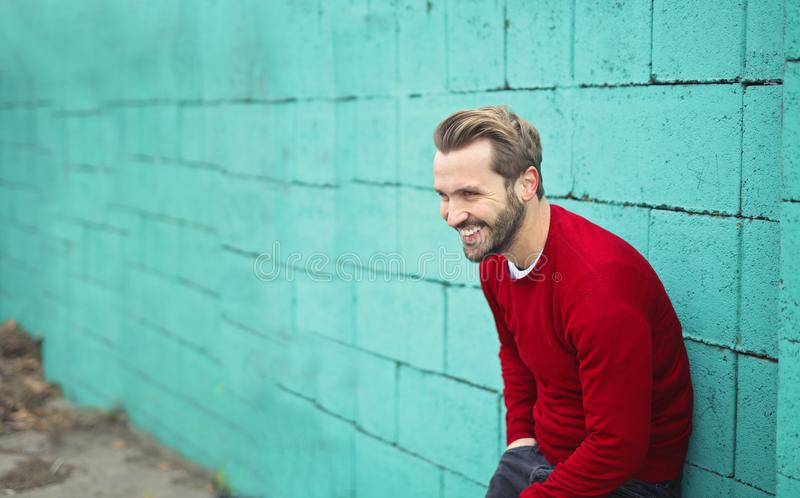 Man Wearing a Red Sweater Leaning on a Blue Wall stock photos