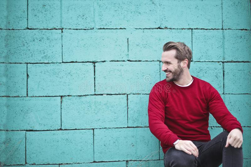 Man Wearing Red Sweatshirt and Black Pants Leaning on the Wall stock images