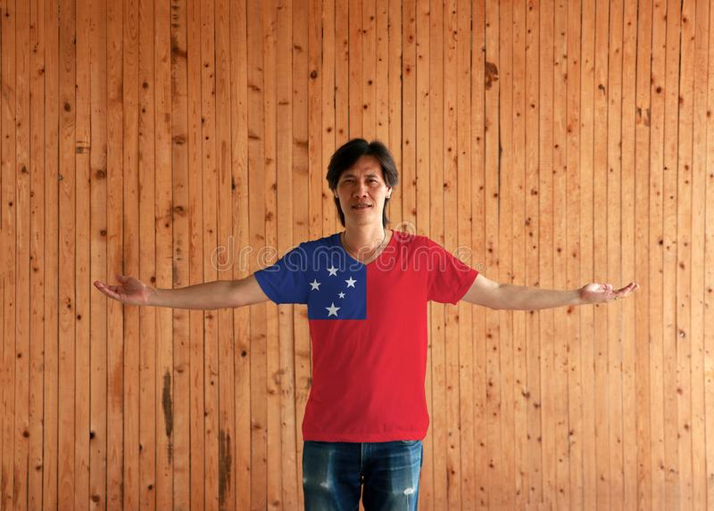 Man wearing Samoa flag color shirt and standing with arms wide open on the wooden wall background royalty free stock photo