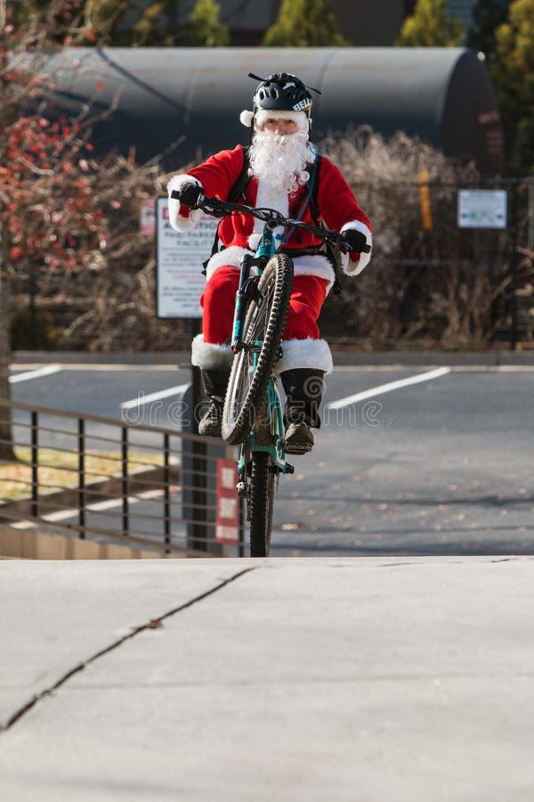 Man Wearing Santa Claus Costume Pops Wheelie On Bicycle stock photography