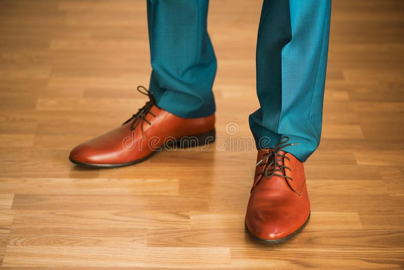 Man wearing shoes on wooden floor. Clothing concept, groom getting ready before ceremony. Body detail of businessman. Man wearing shoes on wooden floor royalty free stock photography