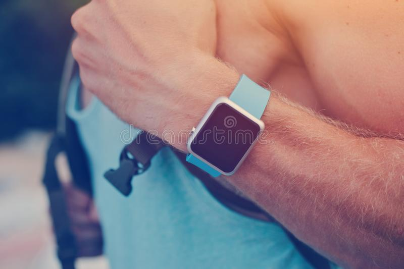 Man wearing smart watch on the wrist. Man with backpack wearing smart watch on the wrist stock image