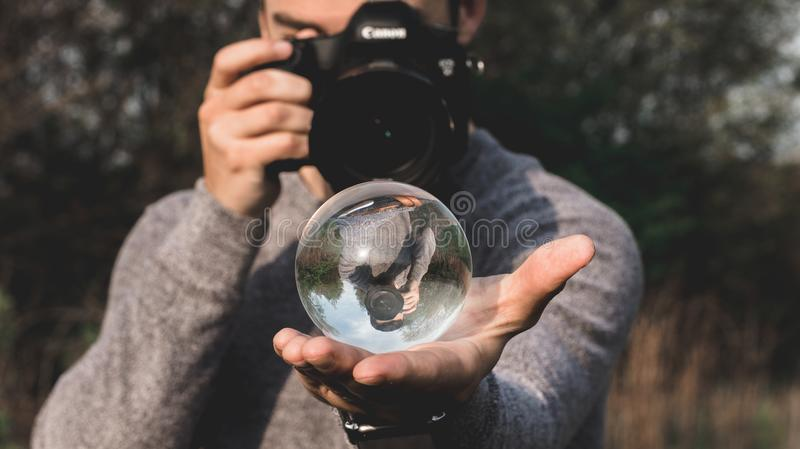 Man Wearing Space-dyed Sweater Holding Water Globe While Holding Black Canon Camera royalty free stock image