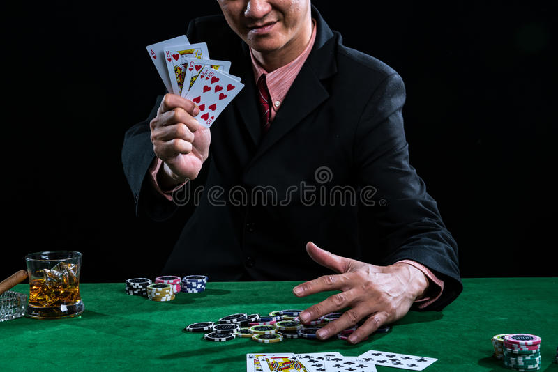 A man wearing a suit holding Hearts Suit Straight Flush on black stock photography