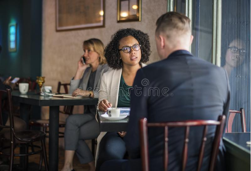 Man Wearing Suit Jacket Sitting on Chair in Front of Woman Wearing Eyeglasses stock photo