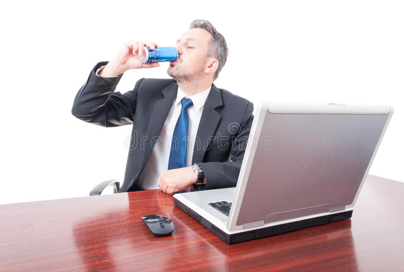 Man wearing suit at office drinking energy drink royalty free stock photography