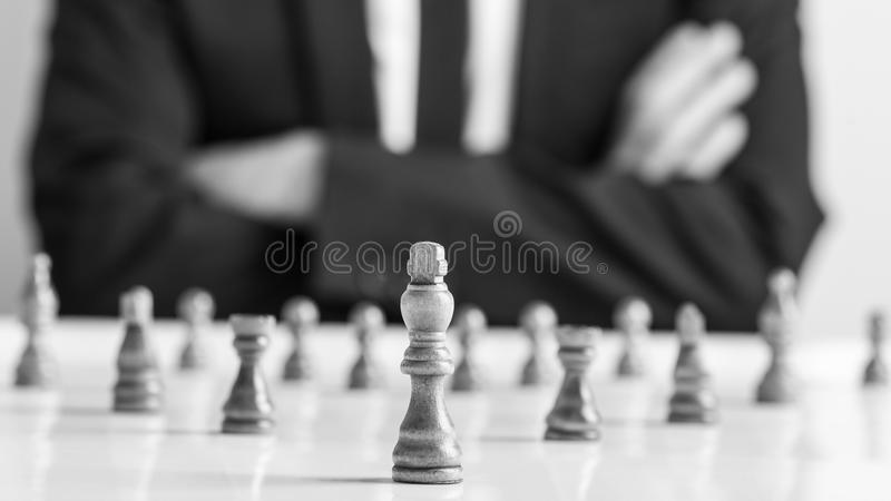 Man wearing suit sitting with folded arms in front of dark chess royalty free stock photos