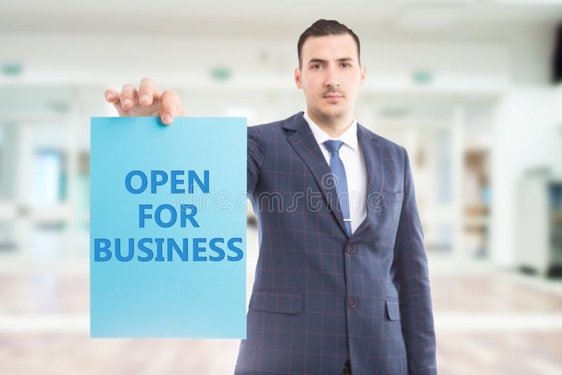 Man holding paper with open for business text stock image